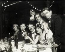 1920, Dîner Dada - Debouts, de gauche à droite : G. Ribemont-Dessaignes, Picabia, non identifiée, G. Auric - Assis : Marthe Chenal, Tristan Tzara, Georges Casella, Germaine Everling
